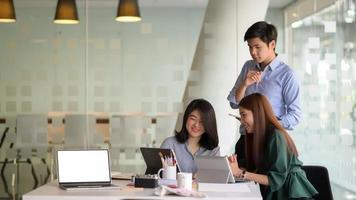 L'équipe commerciale a présenté les concepts avant la réunion avec les clients dans le bureau moderne équipé d'un ordinateur portable. photo