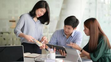 photo recadrée d'une jeune équipe de designers travaillant sur un projet d'application pour smartphone avec utilisation d'une tablette numérique dans une salle de bureau moderne.