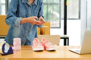 les vendeurs en ligne utilisent leur téléphone portable pour prendre des photos des chaussures envoyées aux clients.