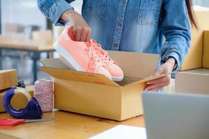 le personnel de livraison des colis emballe les chaussures roses dans la boîte pour la livraison. photo