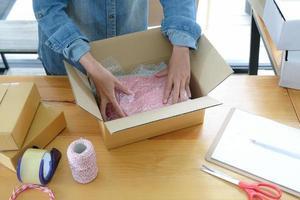 les vendeurs en ligne emballent les produits dans des boîtes pour les expédier aux clients. photo