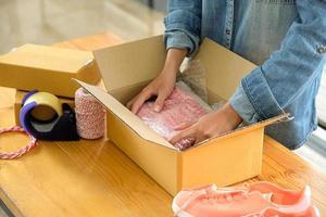 les vendeurs en ligne emballent les chaussures dans des boîtes pour les livrer aux clients. photo
