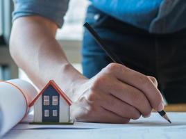 idées de conception de maison, jeune architecte utilisant un crayon noir pour décrire le plan de la maison. photo