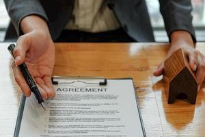 le vendeur manipule le stylo pointant sur le document d'accord pour permettre au client de signer le contrat.concept commercial immobilier. photo