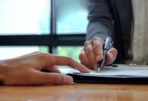 la main du vendeur indique au client d'utiliser le stylo pour signer le contrat. photo