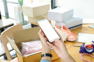le vendeur en ligne utilise un téléphone portable pour prendre une photo des produits dans la boîte envoyée au client.