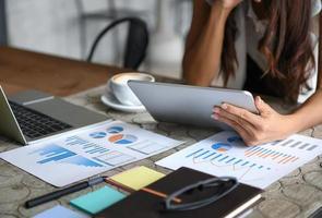 les femmes d'affaires utilisent la tablette pendant leurs loisirs. graphiques, documents posés sur la table. photo
