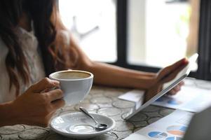 une femme cadre boit du café et utilise une tablette pendant la pause. elle s'assit près de la fenêtre du bureau. photo