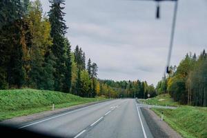 vue sur la route et la forêt d'automne à travers la fenêtre du bus. voyage en voiture photo