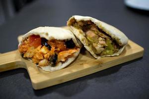 deux délicieux sandwichs pita. l'un avec du fromage feta, des olives noires, de la tomate et du poulet, l'autre avec du saumon et des cornichons photo
