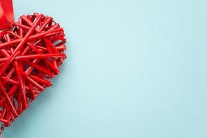 Rotin en osier coeur rouge sur fond bleu photo