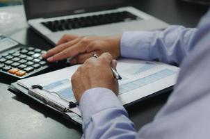 mains d'homme d'affaires tenant des stylos et des documents commerciaux au bureau et à la calculatrice. concept commercial, financier, fiscal et d'investissement. photo