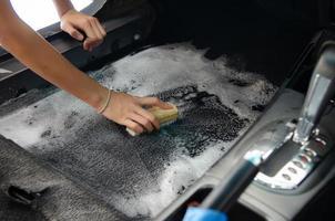 laver le tapis de voiture.détailler à l'intérieur de la voiture moderne.nettoyer en utilisant une brosse et une solution de nettoyage sur le tapis de voiture. photo