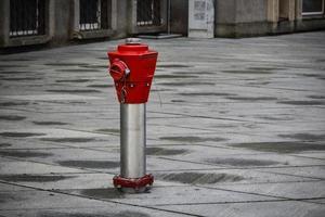 bouche d'incendie rouge debout sur la place carrelée grise de la ville photo