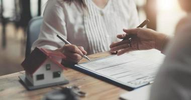 modèle de maison avec agent et client discutant d'un contrat d'achat, d'assurance ou de prêt d'un bien immobilier ou d'une propriété. photo