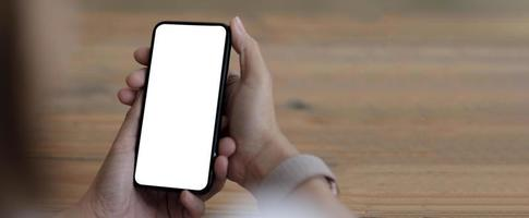 image de maquette téléphone portable à écran blanc vierge. main de femme tenant des textos à l'aide de mobile sur le bureau au bureau à domicile. photo