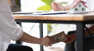 mains de femmes d'affaires en gros plan prenant de l'argent de pot-de-vin sous le concept de table, de corruption et de pot-de-vin photo