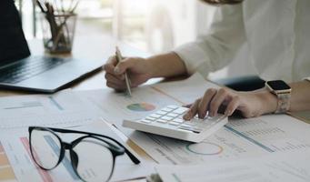 la main de la femme asiatique appuie sur la calculatrice et prépare les informations à corriger pour le rapport. tout en tenant toujours un stylo en argent au doigt. une fois calculé terminé, peut être enregistré immédiatement. photo