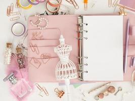 vue de dessus d'un agenda rose avec une jolie papeterie. planificateur glamour rose avec une figurine mannequin blanche. planificateur avec pages ouvertes sur fond blanc et avec de beaux accessoires stylos, boutons, épingles. photo
