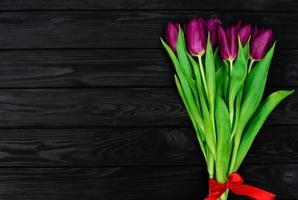bouquet de fleurs de tulipes de printemps violet sur un fond en bois noir. mise à plat. espace de copie. fête des mères. journée internationale de la femme. photo