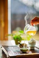 processus d'infusion du thé, cérémonie du thé, une tasse de thé oolong vert fraîchement infusé, lumière douce et chaude. mise au point douce. photo