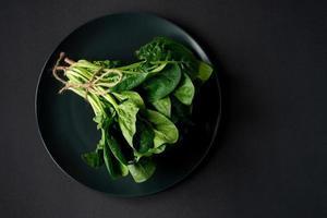 concept de nourriture propre. tas de feuilles d'épinards frais bio dans une assiette sur fond noir. alimentation saine de désintoxication printemps-été. aliments crus végétaliens. espace de copie. photo