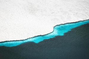 ligne de glace et d'eau dans un lac alpin haut dans les montagnes photo