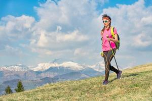 marcher sur les prairies de montagne printanières avec des montagnes enneigées en arrière-plan photo
