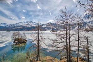 dégel dans la vallée de l'engadine avec îlot dans le lac des alpes suisses photo