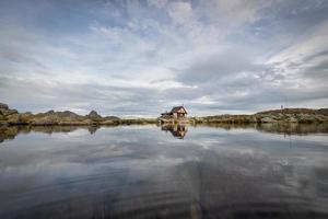 petit ermitage dans les montagnes près d'un lac photo