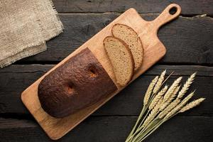 pain frais sur une planche avec du blé sur un fond en bois photo
