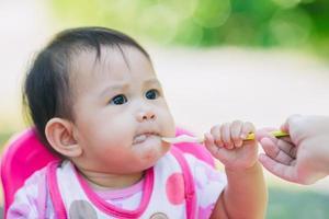 portrait de famille de la mère nourrissant son bébé de 7 mois. concept de temps de qualité de la vie quotidienne avec activité alimentaire chez le nouveau-né. photo