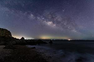 le ciel étoilé au bord de la mer et la voie lactée photo