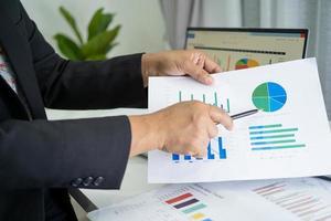 comptable asiatique travaillant et analysant la comptabilité du projet de rapports financiers avec un graphique dans un concept de bureau, de finance et d'entreprise moderne. photo