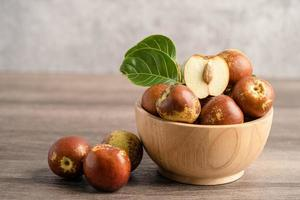 fruits de jujube ou dattes chinoises dans un bol en bois, nourriture saine. photo