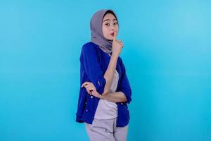 une femme mystérieuse fait un geste de silence regarde au loin raconte un secret portant le hijab isolé sur un mur blanc photo