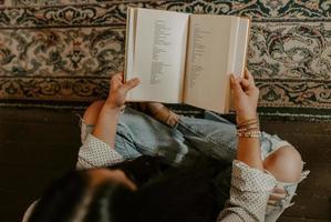 Gros plan sur une jeune femme sud-asiatique assise sur le tapis et lisant un livre photo