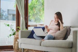 femme asiatique souriante tout en utilisant un ordinateur portable à la maison photo