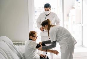 médecins diagnostiquant la pression artérielle d'une femme âgée photo