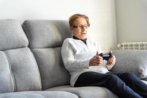 joyeuse femme âgée jouant au jeu vidéo photo