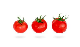 trois tomates flottantes isolées sur fond blanc. photo