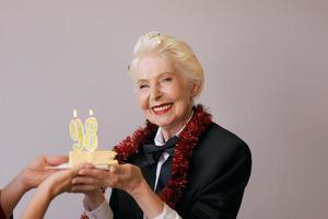Heureuse femme de quatre-vingt-dix-huit ans élégante et joyeuse en costume noir célébrant son anniversaire avec un gâteau. mode de vie, positif, mode, concept de style photo