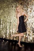 belle femme blonde caucasienne en petite robe noire sur la fête sur fond doré. fête, événement, discothèque, concept de célébration photo