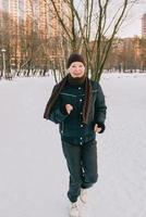 femme âgée au chapeau et veste sportive jogging dans le parc d'hiver de neige. hiver, âge, sport, activité, concept de saison photo