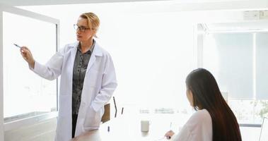 des médecins ou des scientifiques enseignent et expliquent aux étudiants et aux patients qui écrivent à bord photo