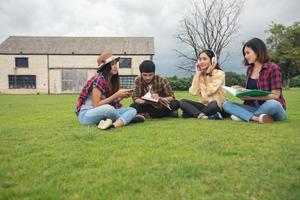 les élèves du groupe sourient et s'amusent et écoutent de la musique, cela aide également à partager des idées sur le travail et le projet. et aussi à revoir le livre avant l'examen en plein air dans le jardin. photo