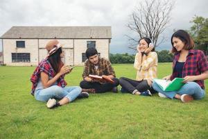 les élèves du groupe sourient et s'amusent et écoutent de la musique, cela aide également à partager des idées sur le travail et le projet et à revoir le livre avant l'examen en plein air dans le jardin. photo
