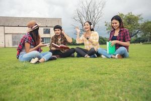 les élèves du groupe sourient et s'amusent cela aide aussi à partager des idées dans le travail et le projet. et aussi revoir le livre avant l'examen en plein air dans le jardin. photo