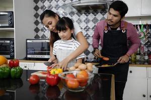 une famille heureuse a papa, maman et leur petite fille qui cuisinent ensemble dans la cuisine photo