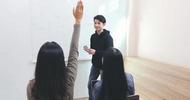 les élèves du groupe lèvent la main pour poser des questions à un ami pour enseigner au tableau blanc en classe photo